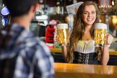 微笑的oktoberfest女服务员用啤酒 库存照片