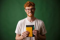 微笑的readhead有胡子的书呆子画象,拿着笔记本和 免版税库存图片