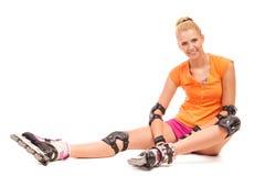 微笑的rollerblader妇女坐地板。 库存照片