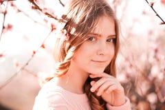 微笑的tenage女孩在桃子庭院里 免版税库存照片