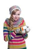 微笑相当佩带五颜六色的被编织的围巾、帽子和手套的女孩,拿着圣诞节礼物被隔绝在白色背景 库存照片