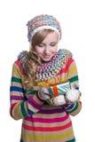 微笑相当佩带coloful被编织的围巾、帽子和手套的女孩,拿着圣诞节礼物被隔绝 图库摄影