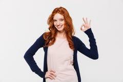 微笑相当显示好姿态的年轻红头发人夫人 免版税库存照片