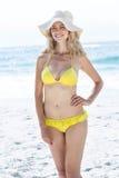微笑相当白肤金发在比基尼泳装佩带的草帽 免版税库存照片