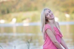 微笑相当白肤金发的少妇对湖边 库存图片