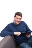 微笑确信的年轻英俊的人拿着数字式片剂和,当坐长沙发时 查出在白色 免版税图库摄影