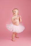 微笑穿一件桃红色芭蕾舞短裙的一个岁女孩 免版税库存照片