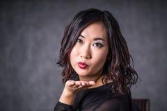 微笑美丽和可爱的成熟年轻亚裔深色的妇女送飞吻和,当佩带黑色时 图库摄影