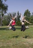 微笑美丽和英俊的女孩跳跃愉快 体育在公园 库存照片