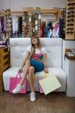 微笑美丽的女售货员,当坐在服装店时 妇女的喜爱的消遣 购物的早晨好 图库摄影