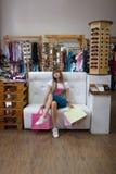微笑美丽的女售货员,当坐在服装店时 妇女的喜爱的消遣 购物的早晨好 库存图片