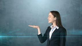 微笑美丽的女实业家看她的手和,灰色背景 免版税库存照片