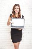 微笑美丽的妇女,当提出一台全新的膝上型计算机时 免版税库存图片