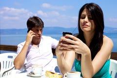 微笑美丽的妇女,当texting在移动电话时 免版税图库摄影