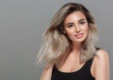 微笑美丽的少妇的画象摆在有吸引力白肤金发与在灰色背景的飞行头发 免版税库存照片
