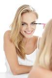微笑美丽的白肤金发的妇女,当应用染睫毛油时 免版税库存图片