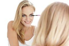 微笑美丽的白肤金发的妇女,当应用染睫毛油时 库存照片