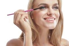微笑美丽的白肤金发的妇女,当应用染睫毛油时 免版税图库摄影