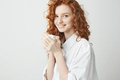 微笑美丽的红头发人的女孩画象拿着看在白色背景的杯子照相机 库存照片