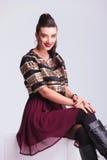 微笑美丽的年轻时尚的妇女,当坐时 免版税库存照片