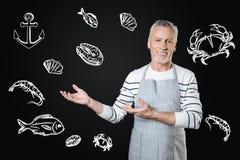 微笑老练的厨师,当提供鲜美海洋食物时 图库摄影
