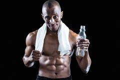 微笑肌肉的人画象有毛巾的在脖子上,当拿着水瓶时 免版税库存照片