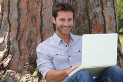微笑膝上型计算机的人使用 免版税图库摄影