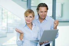 微笑英俊,成熟商人和确信的女实业家,研究在现代办公楼的便携式计算机 免版税库存图片