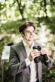 微笑衣服的商人与看在他的市场上的双筒望远镜竞争者在绿色公园 到达天空的企业概念金黄回归键所有权 图库摄影