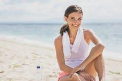 微笑运动的妇女,当坐沙子时 免版税库存图片