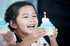微笑逗人喜爱的亚裔儿童的女孩和吹她的生日杯形蛋糕 免版税库存照片