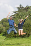 微笑逗人喜爱的夫妇跳跃和 库存图片