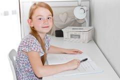 微笑逗人喜爱的小女孩在家学习和 库存照片