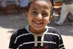 微笑逗人喜爱的英俊的男孩摆在和 免版税库存照片