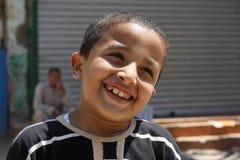 微笑逗人喜爱的英俊的男孩画象摆在和 免版税库存照片