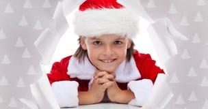 微笑通过在包装纸的孔的愉快的圣诞节男孩 免版税图库摄影