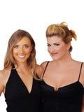 微笑黑色白肤金发的礼服二名妇女 免版税库存照片