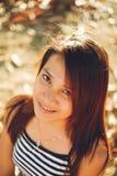 微笑,与好的阳光的年轻亚裔妇女美丽的画象  免版税库存照片