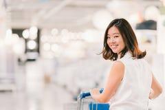 微笑,与购物车、购物中心或者百货商店场面,迷离bokeh背景的美丽的年轻亚裔妇女 库存图片
