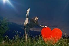 微笑,卷曲舞蹈家在象草的领域执行垂直的旁边分裂 免版税图库摄影