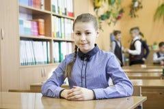 微笑,当坐对有同学的书桌的年轻女小学生画象在背景中时 免版税库存图片