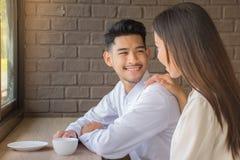 微笑,当坐对桌和饮用的咖啡的年轻甜心在咖啡店/幸福和健康关系概念时 图库摄影