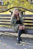 微笑,快乐的女孩谈话在电话户外在长凳 库存图片