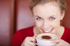 微笑,美丽的妇女饮用的热奶咖啡 免版税库存照片