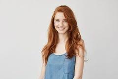 微笑年轻可爱的红头发人的女孩看照相机 免版税库存图片