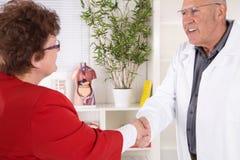 微笑医生向他的女性患者问好 免版税库存图片