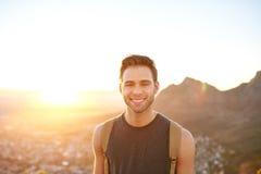 微笑年轻的人,当在清早自然远足时 免版税库存照片