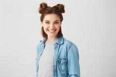 微笑年轻美丽的十几岁的女孩画象用两个小圆面包看在白色背景的照相机 图库摄影