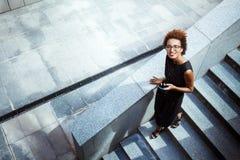 微笑年轻美丽的非洲的女孩拿着沿着走台阶的电话 免版税库存照片