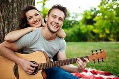 微笑年轻美好的夫妇,基于野餐在公园 免版税库存图片